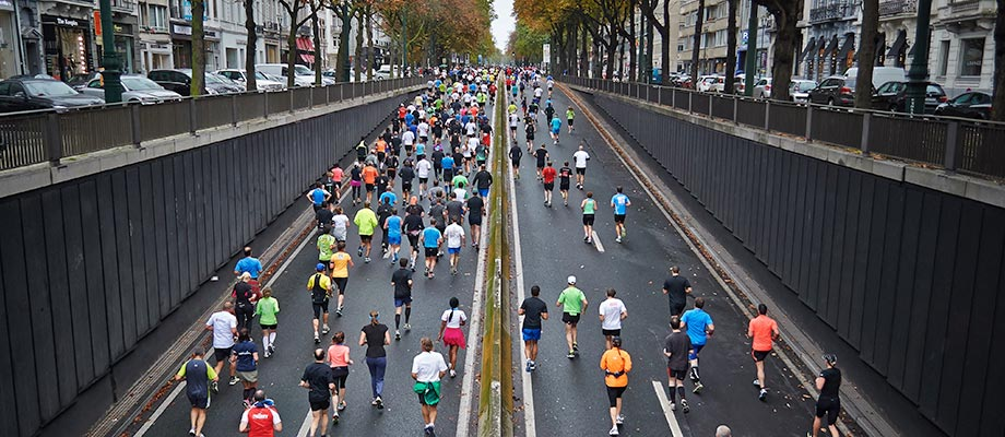 A large group of marathon runners running down a street.