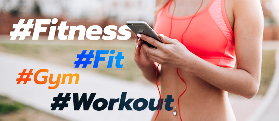 A fit girl holding her phone with the hashtags #Fitness #Fit #Gym #Workout
