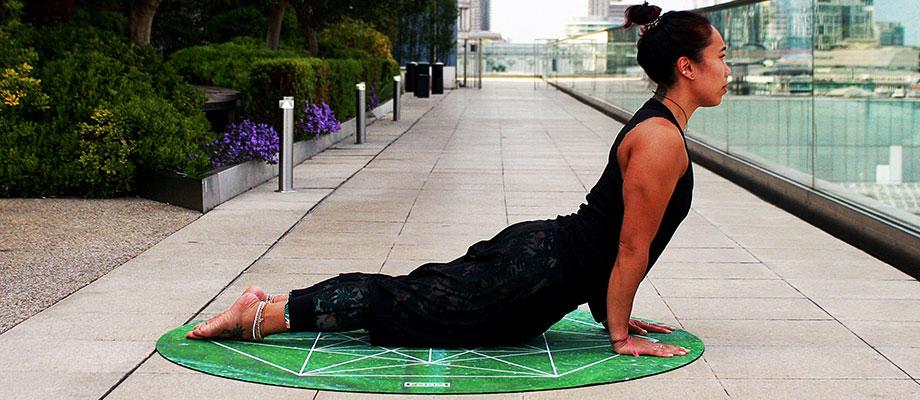 Asian woman performing a Cobra Pose in yoga